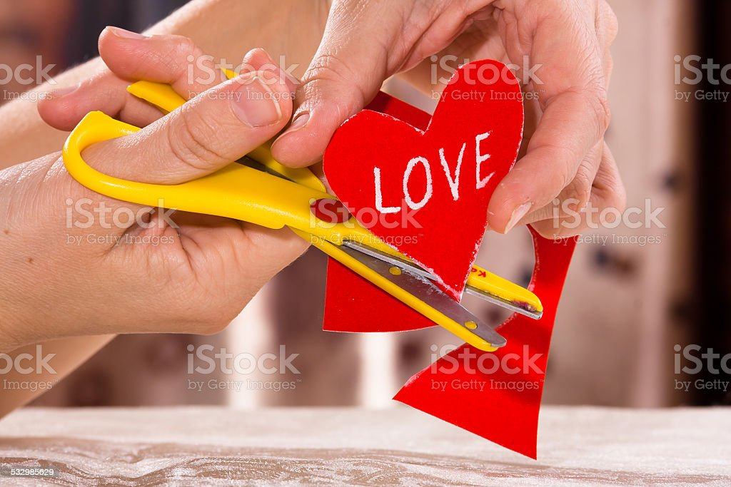 scissoring out paper heart for Valentine's day stock photo