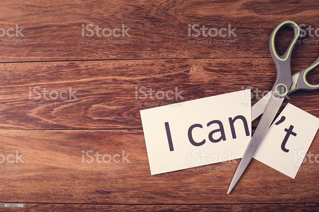 Scissors and word 'I can't' on wooden background stock photo
