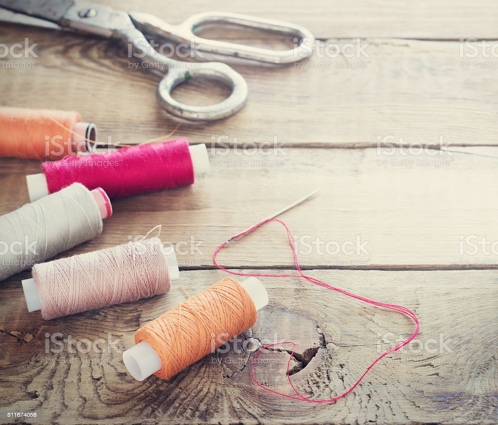 Scissors, bobbins with thread and needles. stock photo