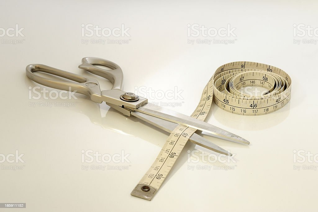 scissors cutting a measuring tape royalty-free stock photo