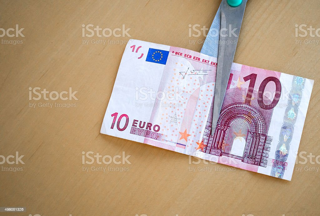 Scissors Cutting a Ten Euro (EUR) Banknote Background royalty-free stock photo