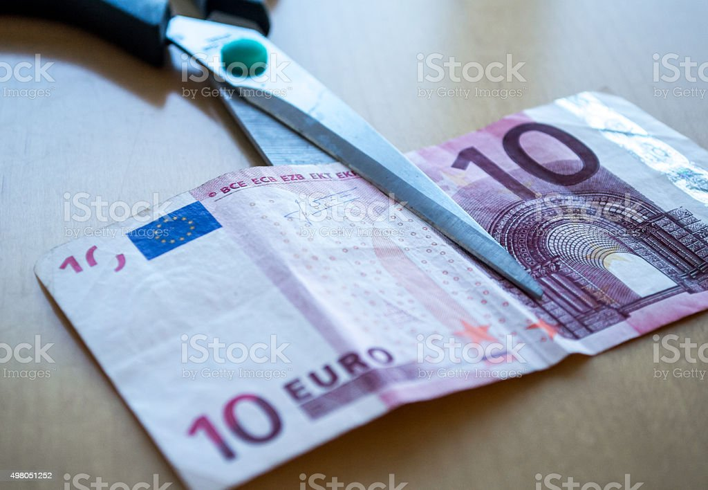 Scissors Cutting a Ten Euro (EUR) Banknote Close Up royalty-free stock photo