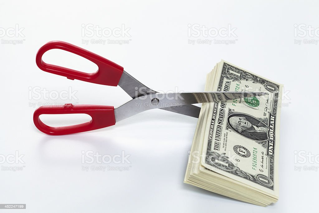 scissors cutting dollar bills stock photo