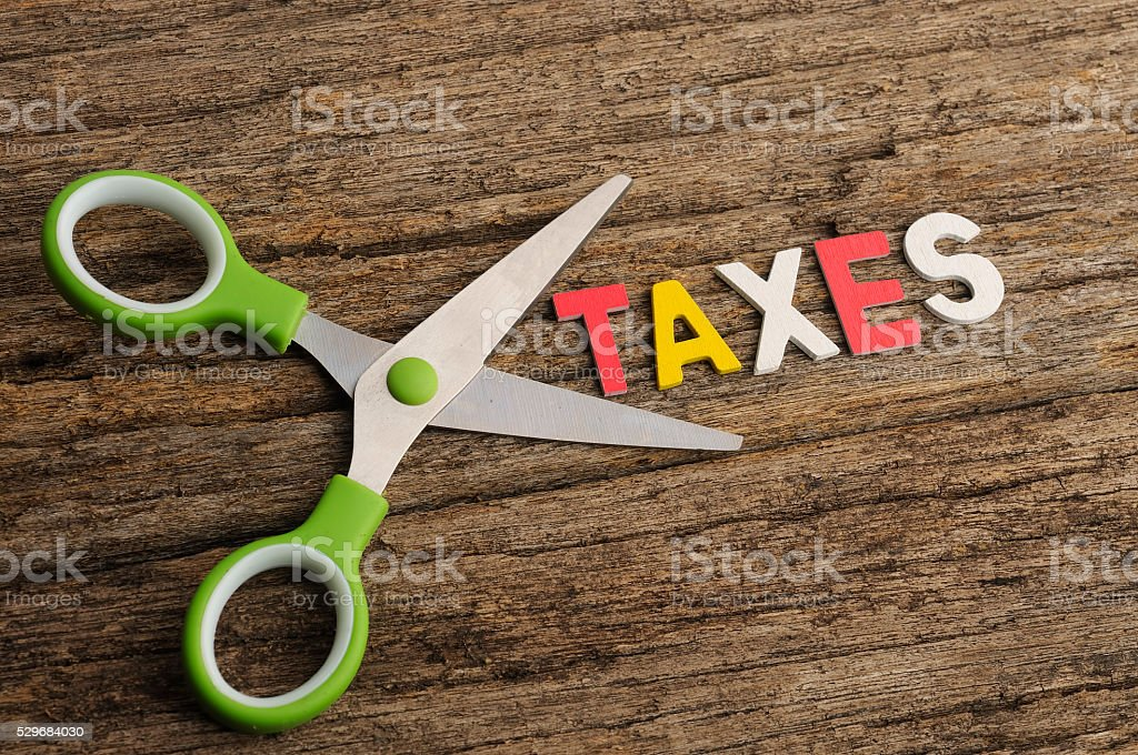 Scissors With TAXES Word on Wooden Background stock photo