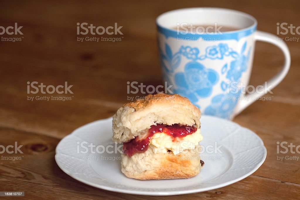 Scone filled with butter and jam next to a cup of coffee stock photo