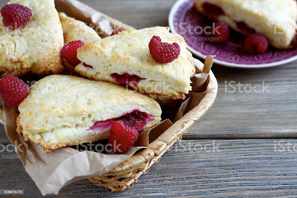 Scone with raspberry in a wicker basket stock photo