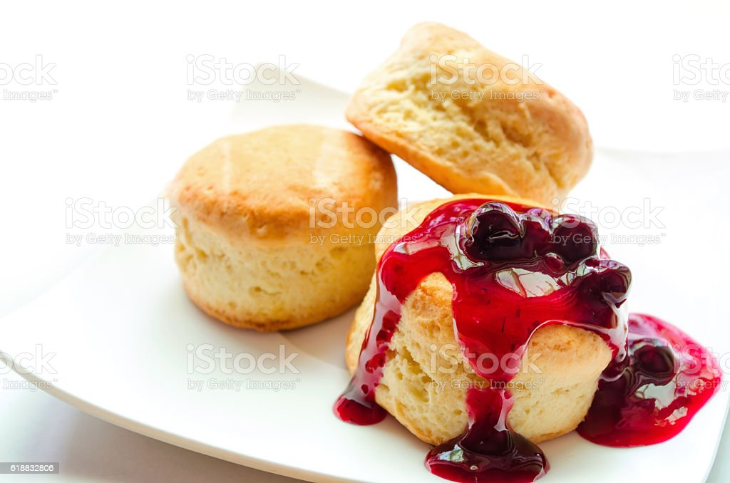 Scones with blueberry sauce on white plate. stock photo