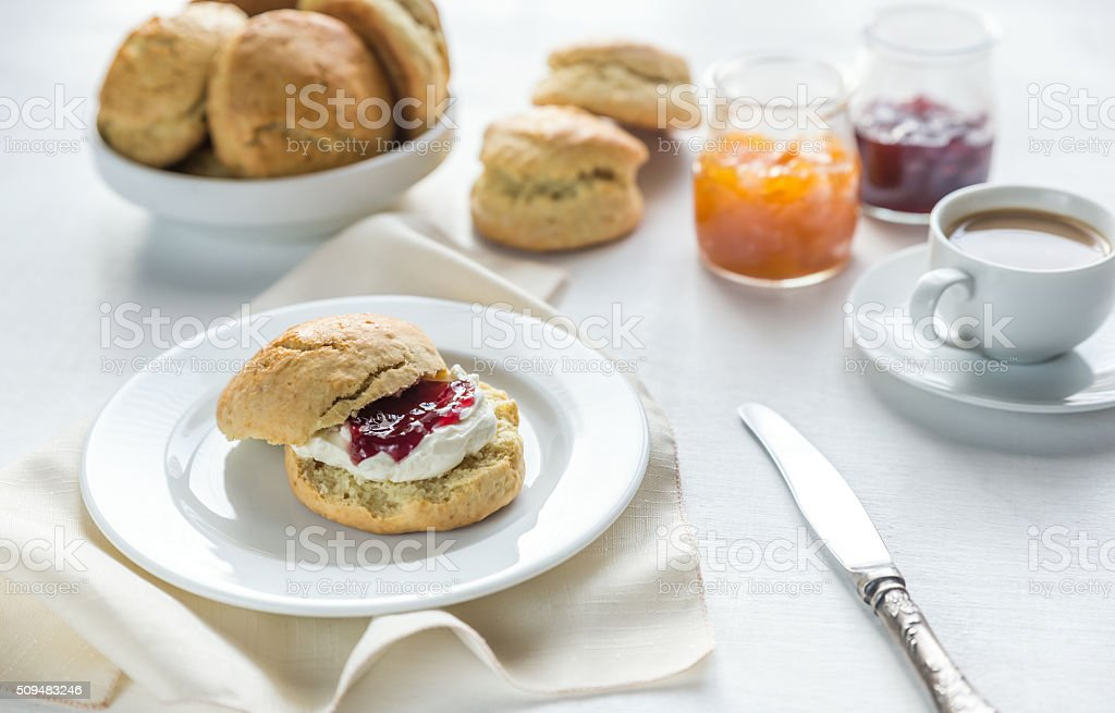 Scones with cream and fruit jam and cup of coffee stock photo