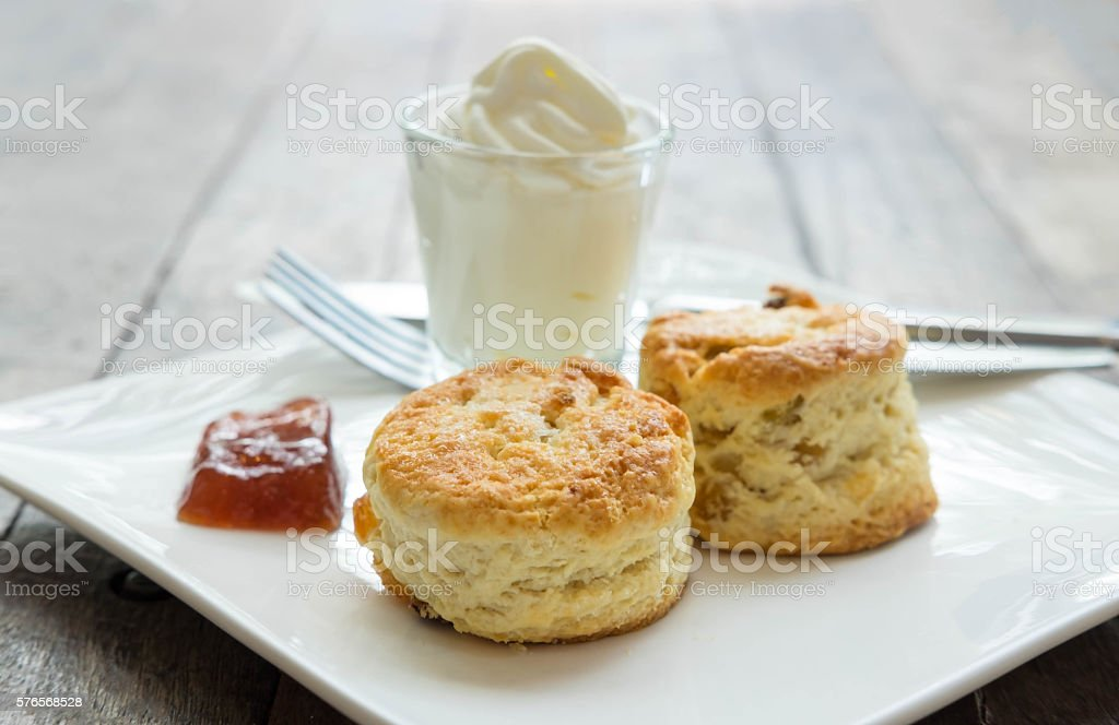 Scones with cream and jam in white plate stock photo