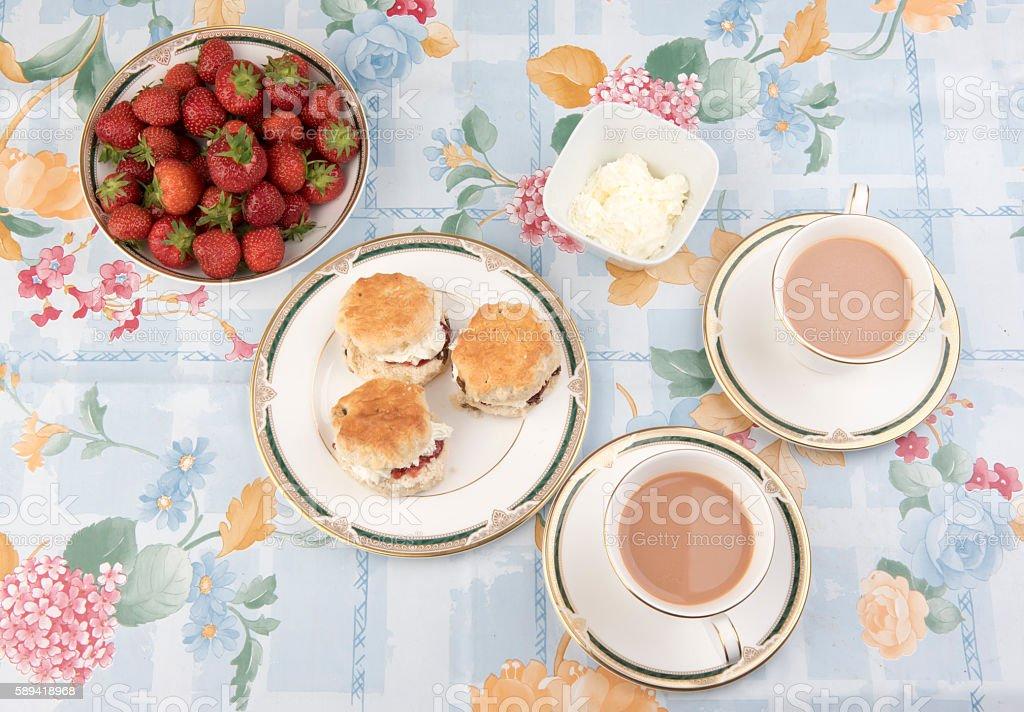 Scones with jam, cream and strawberries with tea stock photo