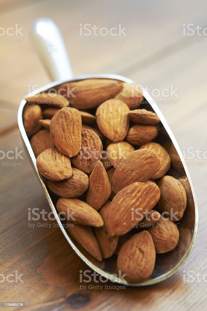 Scoop Of Almonds On Wooden Surface stock photo