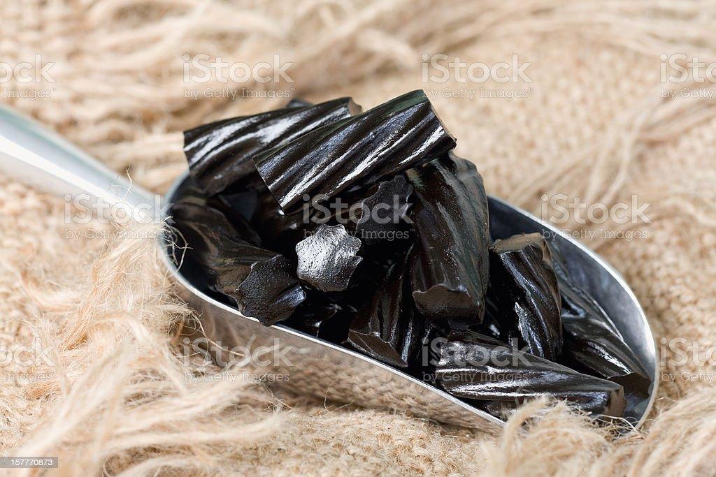 Scoop of Black Liquorice Candy on Burlap stock photo
