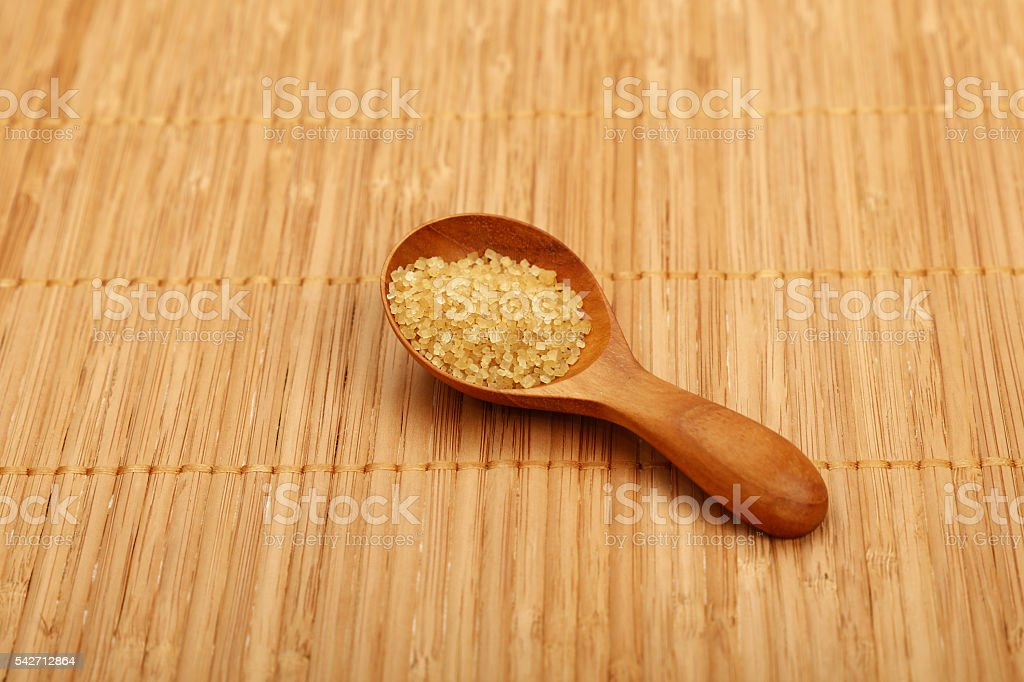 Scoop of brown cane sugar on bamboo mat stock photo