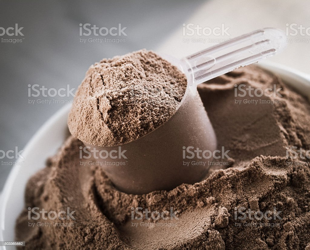 Scoop of chocolate flavor protein powder stock photo