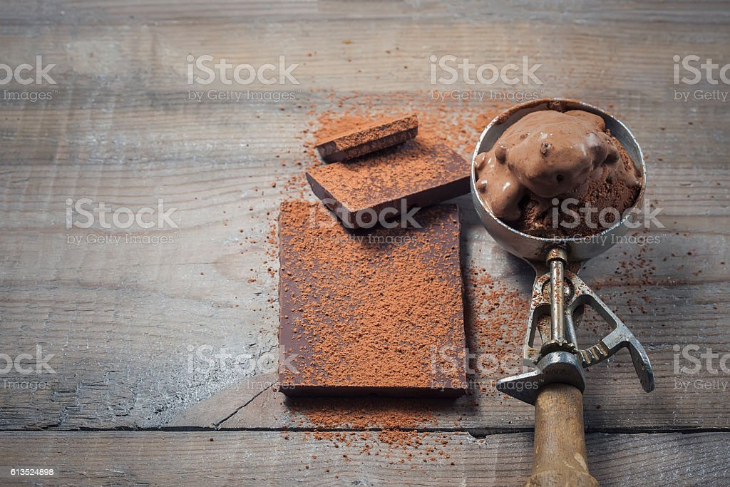 Scoop of chocolate ice cream on rustic wooden background. stock photo