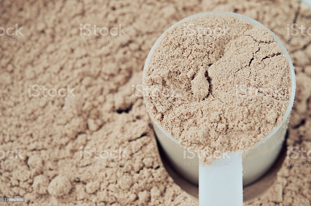 A scoop of chocolate protein powder in a measure cup stock photo