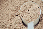 A scoop of chocolate protein powder in a measure cup