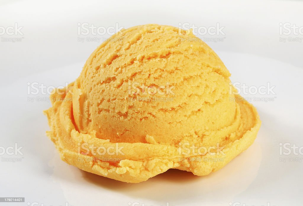 Scoop of orange sherbet on a white dish stock photo
