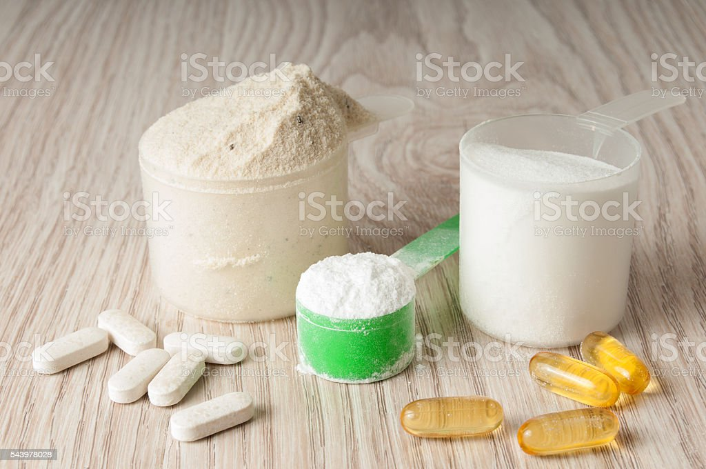 scoop of protein, bcaa and creatine, omega3 in pills stock photo