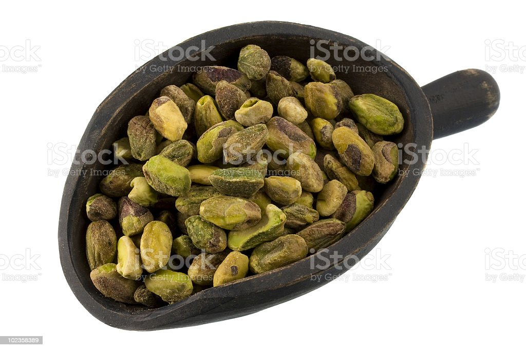 scoop of raw shelled pistachio nuts stock photo