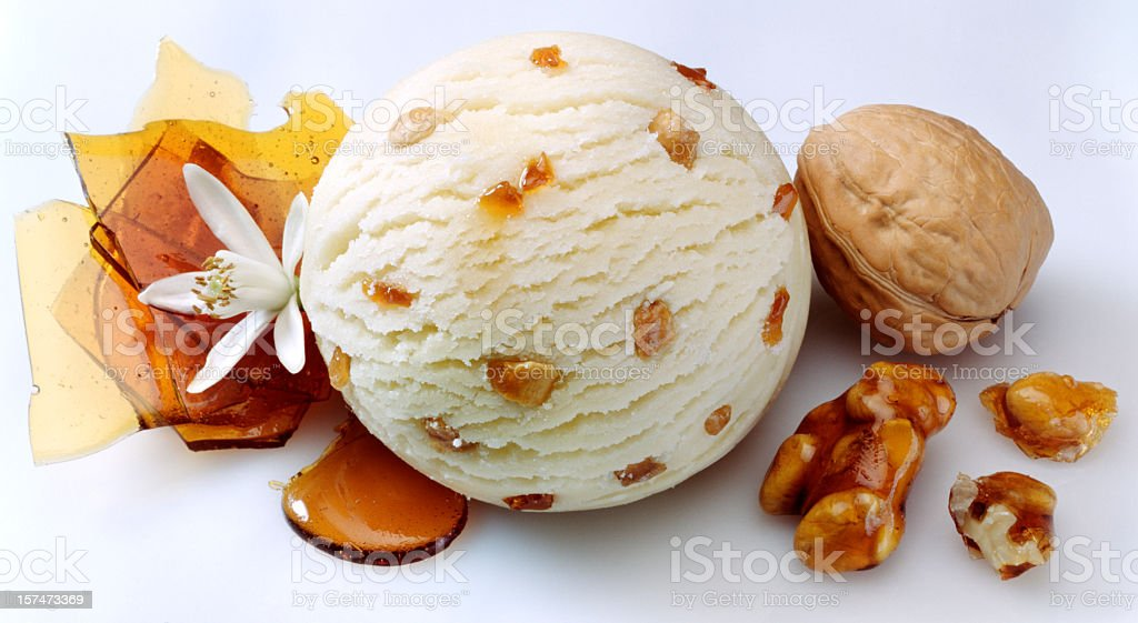 A scoop of vanilla ice cream with nuts and caramel  stock photo