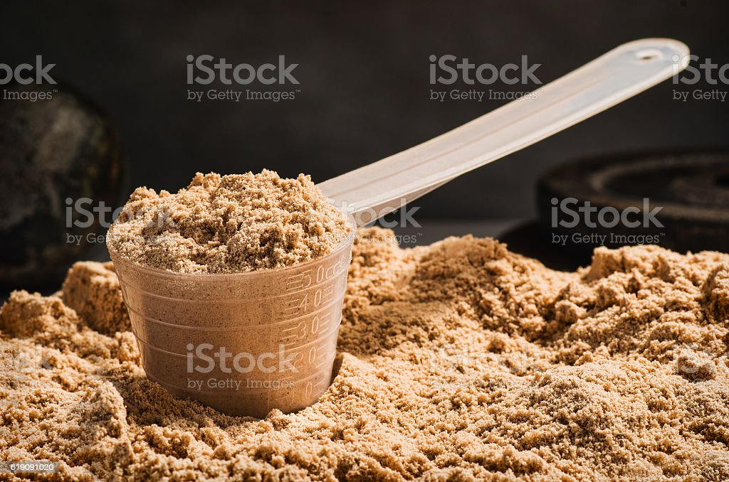 Scoop of whey protein on black background. Chocolate flawour stock photo