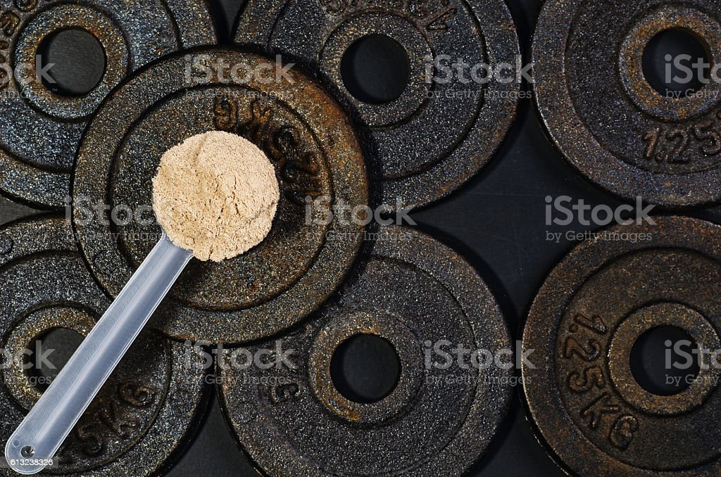 Scoop of whey protein on black background. Top view stock photo