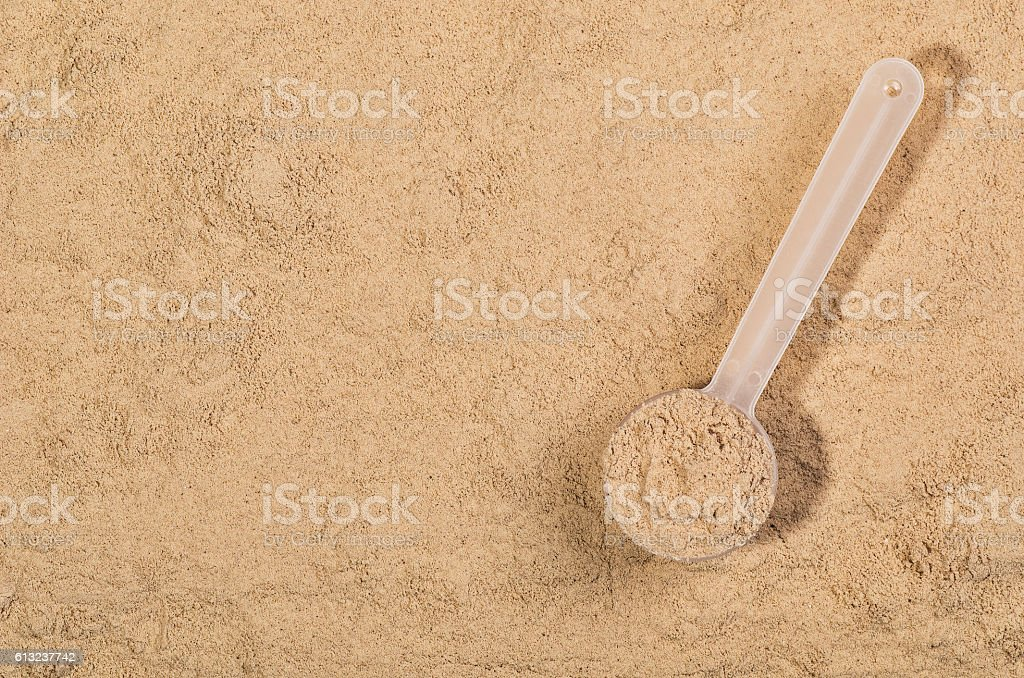 Scoop of whey protein on textured background. Top view stock photo