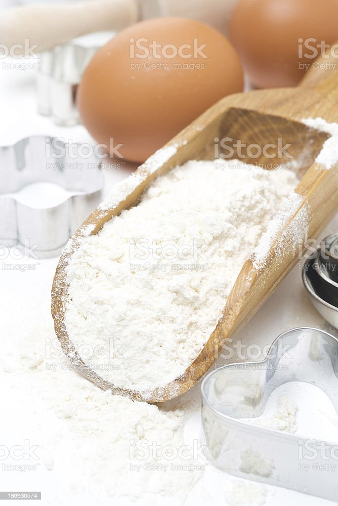 scoop with wheat flour, rolling pin, eggs and cookie cutters royalty-free stock photo