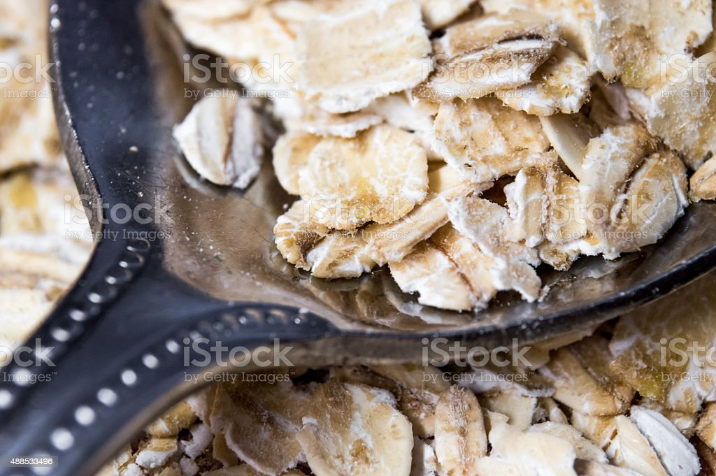 Scooping Traditional Jumbo Rolled Oats with a Spoon Close Up royalty-free stock photo