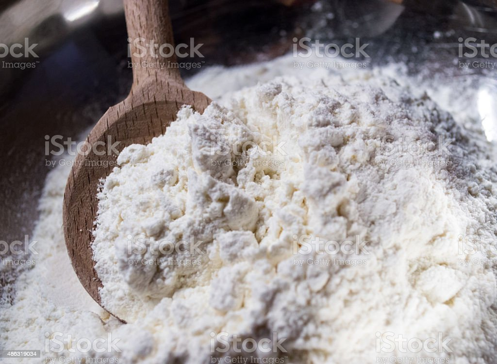 Scooping White Flour with a Wooden Spoon Front View royalty-free stock photo