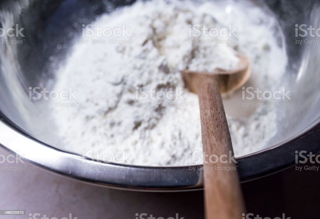 Scooping White Flour with a Wooden Spoon royalty-free stock photo