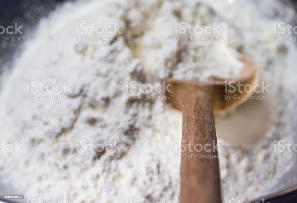 Scooping White Flour with a Wooden Spoon POV royalty-free stock photo