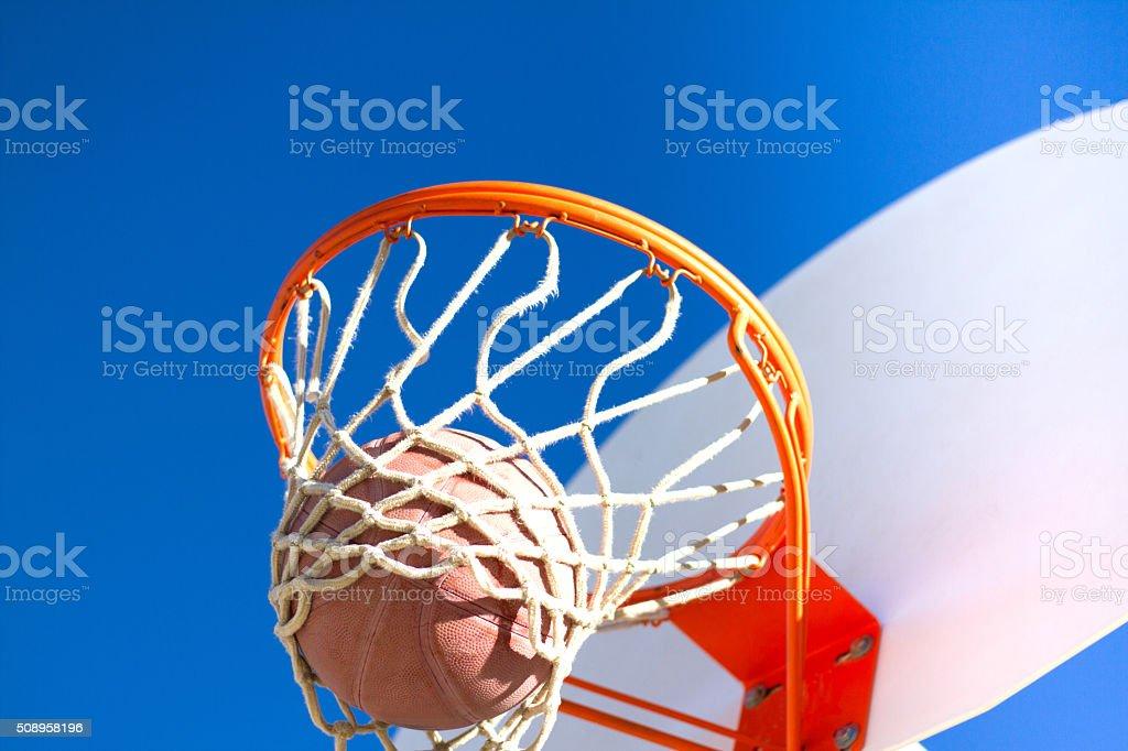Scoring: Basketball Falling Through Hoop; Indigo Sky (Close-Up) stock photo