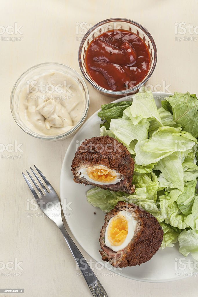Scotch eggs cut in halves on a plate stock photo