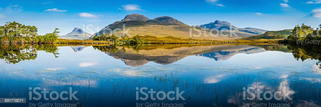 Scotland blue loch reflecting green mountains rocky peaks Highlands panorama stock photo