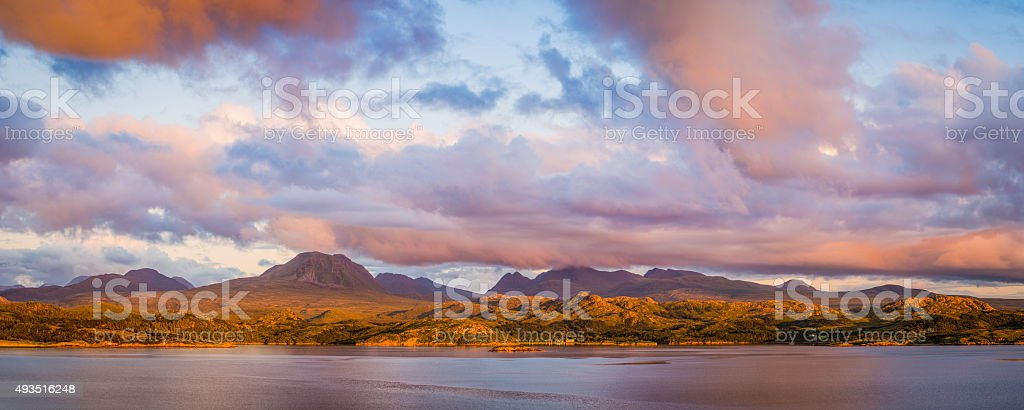 Scotland golden sunset across loch to Highlands mountain peaks panorama stock photo