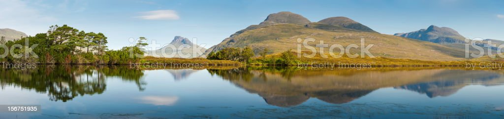 Scotland Highland mountain peaks reflecting in tranquil loch stock photo