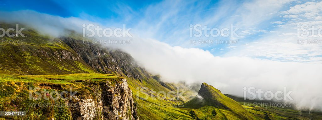 Scotland mist rolling over green Highlands mountain panorama Quiraing Skye stock photo