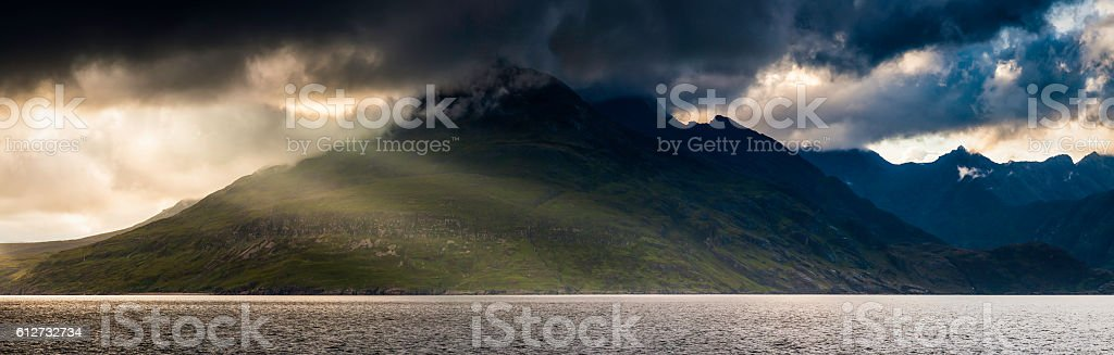 Scotland rays of sunlight stormclouds over Cuillin mountains panorama Skye stock photo