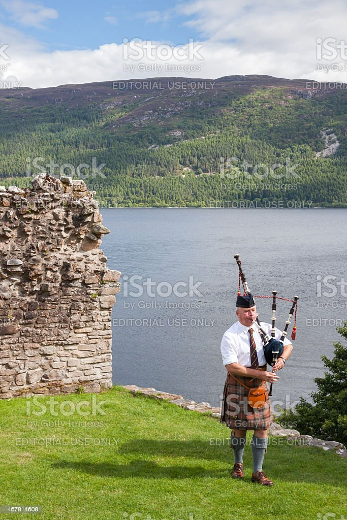 URQUHART CASTLE, Scottish Highlander wearing kilt and playing Bagpipe stock photo