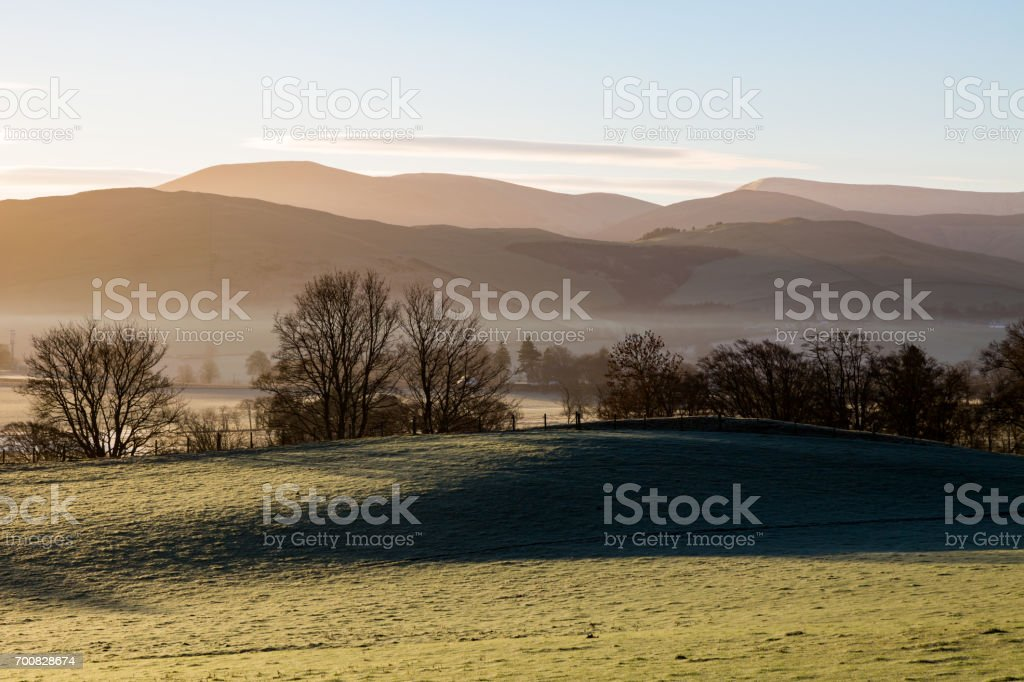 Scottish highlands in sunrise light with fog in middle stock photo
