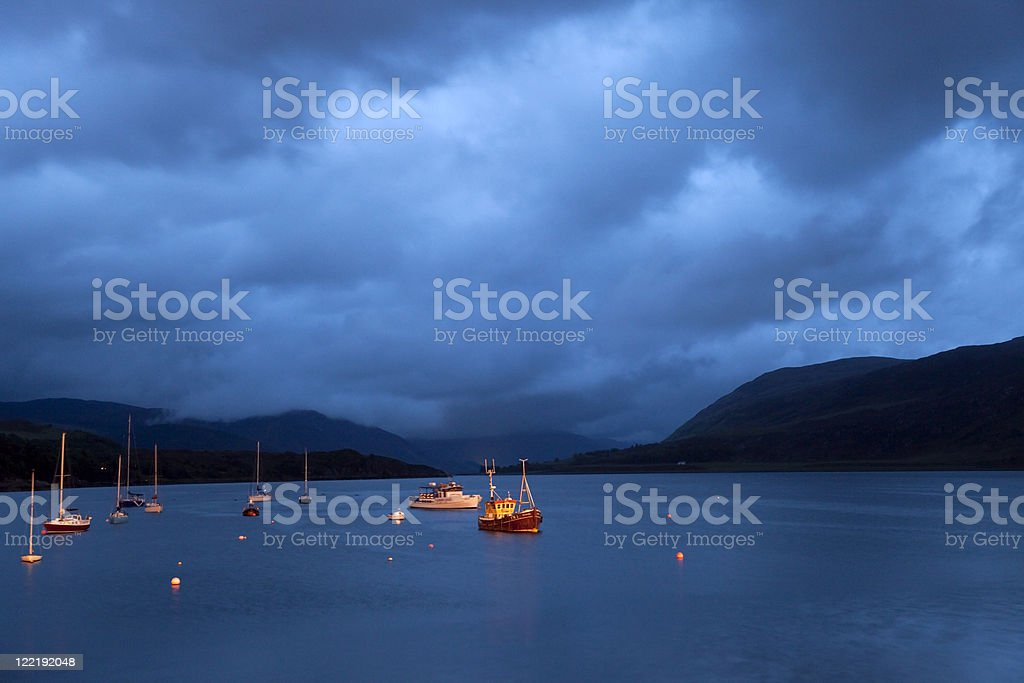 Scottish Loch with boats at night royalty-free stock photo