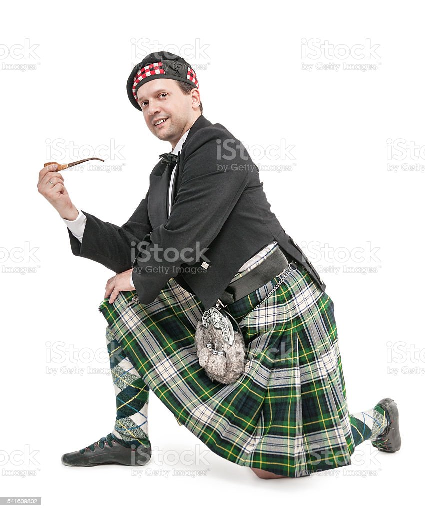 Scottish man in traditional costume with smoking pipe stock photo