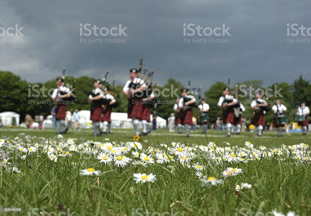Scottish Pipe Band marching on the grass royalty-free stock photo
