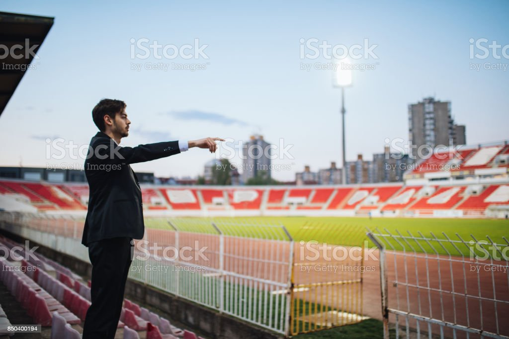 Scout standing on stadium and watching game stock photo