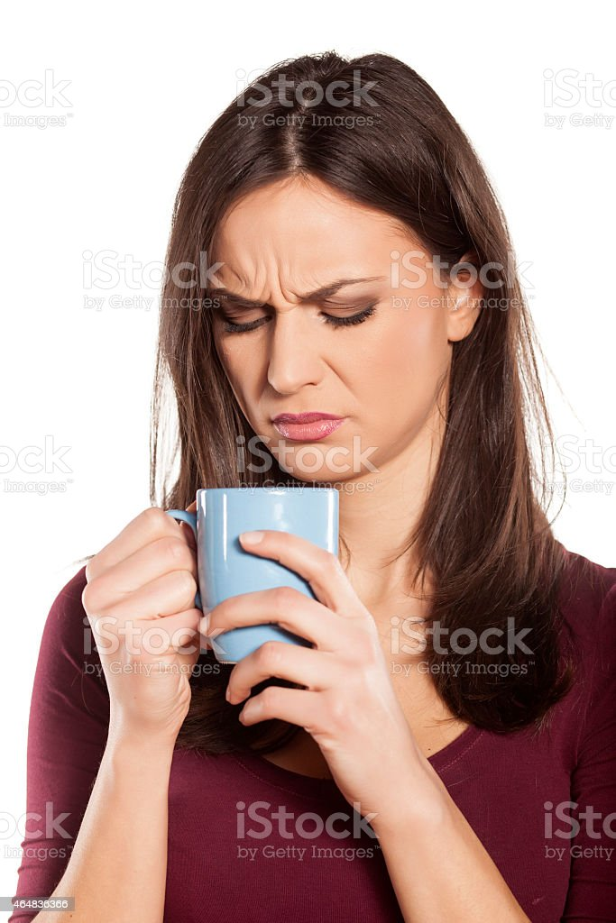 Scowling woman looking disgusted by the smell of her drink stock photo