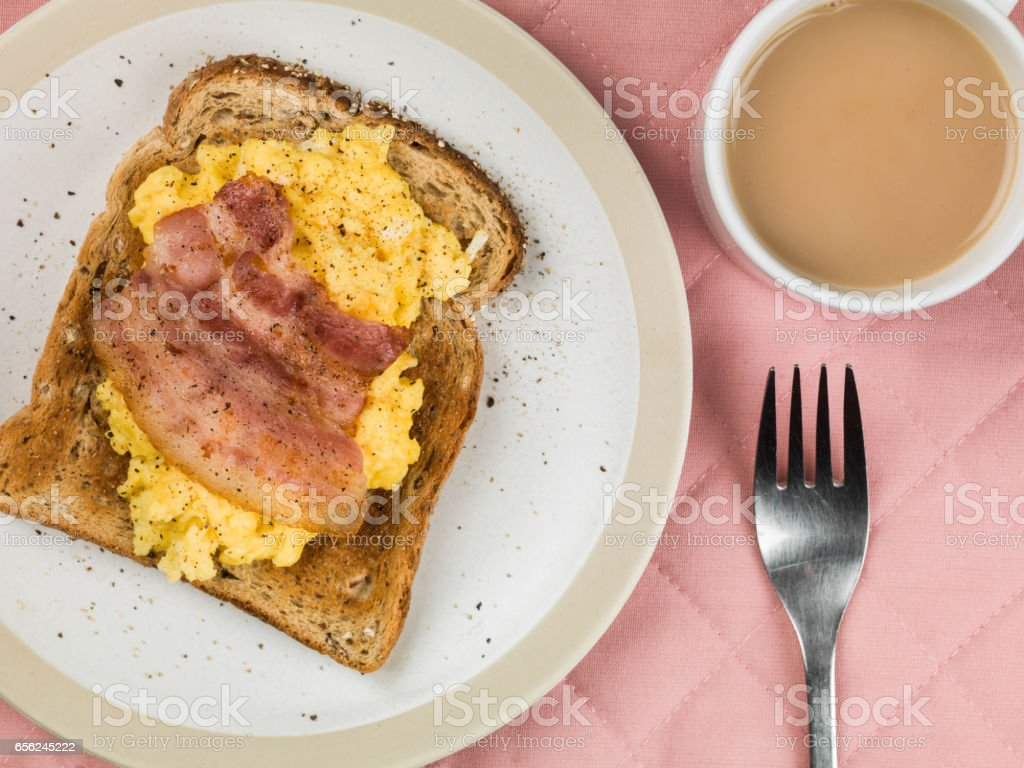 Scrambled Egg on Toast With Bacon and a Mug of Tea stock photo