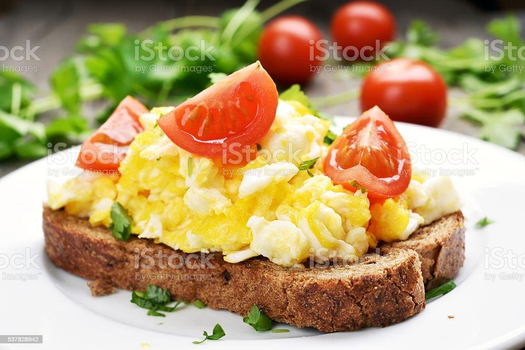 Scrambled eggs and tomato slices on bread stock photo