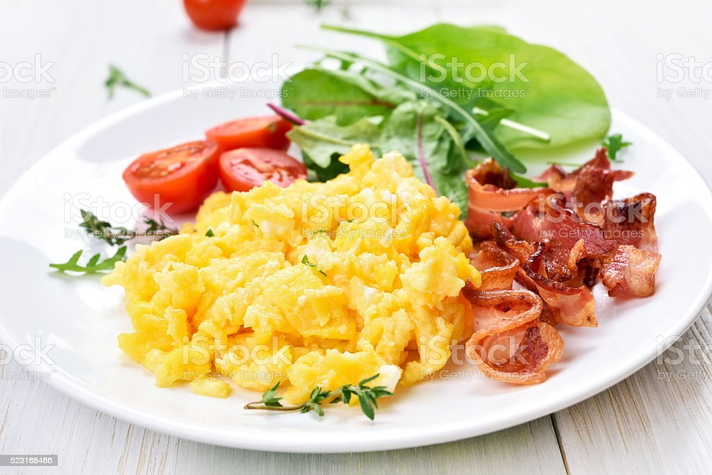 Scrambled eggs, bacon and vegetable salad stock photo